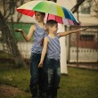 Two boys with rainbow umbrella in park — Stock Photo