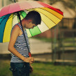 Sad boy withl rainbow umbrella — Stock Photo