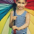 Little girl with a rainbow umbrella in park — Stock Photo #27885677