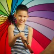 Little girl with a rainbow umbrella in park — Stock Photo #27885685