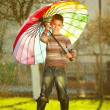 Little girl with a rainbow umbrella in park — Stock Photo #27885755