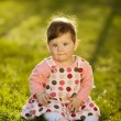 Baby sitting on grass in garden — Stock Photo