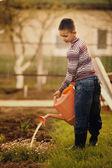 Little helper watering flowers in the garden — Foto de Stock