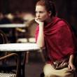 Beautiful girl waiting at a table in a cafe — Stock Photo