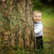 Baby hiding behind tree in park — Stock Photo