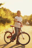 Little boy with bike on sunset — Stock Photo