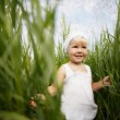 Cute little girl in high grass — Stock Photo