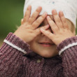 Photo: Little girl is playing hide-and-seek