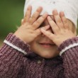 Stock Photo: Little girl is playing hide-and-seek