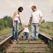 Parents with baby on railroad — Stock Photo