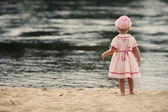 Little girl standing with her back on the beach — Stock Photo