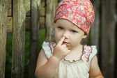 Cute mischievous toddler girl with finger in her nose — Stock Photo
