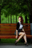Young beautiful girl sitting on bench — Stock Photo