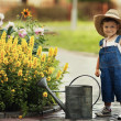 Stock Photo: Little boy watering flowers