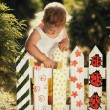 Little girl paints a fence — Stock Photo