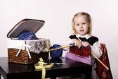 Little girl knitting scarf — Stock Photo