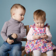 Boy and girl playing with mobile phones — Stock Photo