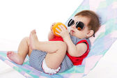 Baby lying on lounger isolated on white — Stock Photo