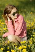 Beautiful girl with sunglasses in dandelion field — Stock Photo