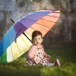 Little girl with a rainbow umbrella in park — Stock Photo #42848817