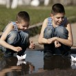 Little boys playing with paper boats in puddle — Stock Photo