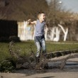 Little boy jumping in puddle — Stock Photo #42849301