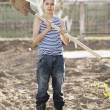 Happy boy working with shovel in garden — Stock Photo #42849521