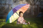 Little girl with a rainbow umbrella in park — Stockfoto