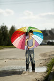 Little boy with a rainbow umbrella in park — Stockfoto