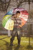 Ragazzo felice con un ombrello arcobaleno nel parco — Foto Stock