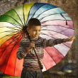 Happy boy with a rainbow umbrella in park — Stock Photo