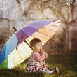 Little girl with a rainbow umbrella in park — Stock Photo #42850581