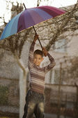 Happy boy with a rainbow umbrella in park — Stockfoto