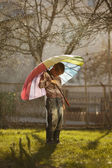 Sad boy with colorful rainbow umbrella — Stock Photo