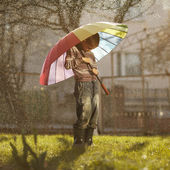 Sad boy with colorful rainbow umbrella — Stock Photo