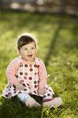 сладкий ребенок сидел на траве в саду — Стоковое фото