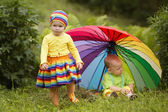 Little children under colorful umbrella — Stock Photo
