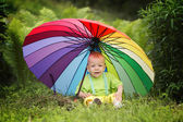 Cute boy under colorful umbrella — Stock Photo
