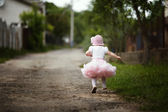 Little girl in dress running away — Стоковое фото