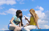 Two girls with the phone on the sky background — Stock Photo