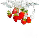 Strawberries being thrown into water — Stock Photo