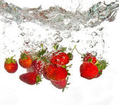 Strawberries falling into water — Stock Photo