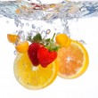 Stock Photo: Fruit falling into water
