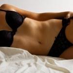 vrouw in zwarte ondergoed leggen op bed — Stockfoto