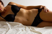 Woman in black underwear lay on bed — Stock Photo