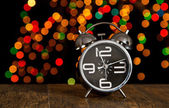Bokeh spots of lights with alarm clock on wood — Stock Photo