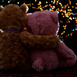 Two Teddie bear sitting holding bokeh background — Stock Photo #27527363