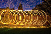 Burning steel wool spin in circles to make patterns — Stock Photo