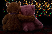Two Teddie bear sitting holding bokeh background — Stock Photo