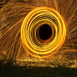 Burning steel wool spin in circles to make patterns — Stock Photo #27629489